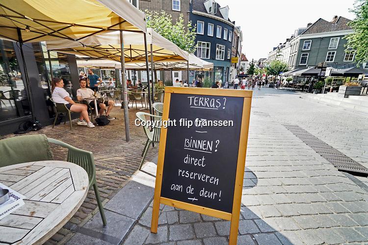 Nederland, Nijmegen, 12-8-2020 Bij een cafe in de stad heeft men formulieren waar bezoekers, gasten, hun gegevens moeten invullen vanwege een eventueel contactonderzoek bij geconstateerde corona . Dit is een van de aanvullende maatregelen, coronamaatregelen om een tweede golf en mogelijke sluiting van de horeca te voorkomen . Foto: ANP/ Hollandse Hoogte/ Flip Franssen