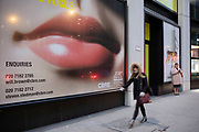 Giant advertising face with full lips dominating people passing below on Fenchurch Street in the City of London on 5th February 2020 in London, England, United Kingdom. The City of London is a city, county and a local government district that contains the historic centre and the primary central business district CBD of London.