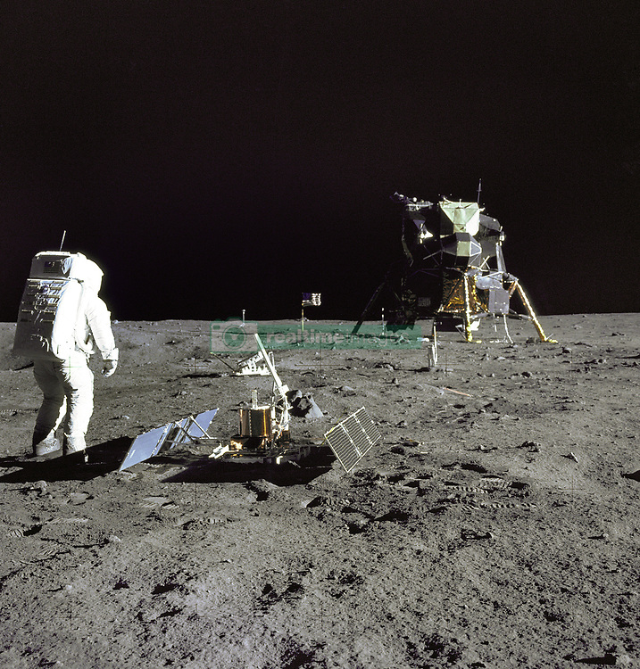 """The Moon - (FILE) - Astronaut Edwin E.""""Buzz"""" Aldrin Jr., Lunar Module pilot, is photographed during the Apollo 11 extravehicular activity on the Moon on Sunday, July 20, 1969. He has just deployed the Early Apollo Scientific Experiments Package (EASEP). In the foreground is the Passive Seismic Experiment Package (PSEP); beyond it is the Laser Ranging Retro-Reflector (LR-3); in the center background is the United States flag; in the left background is the black and white lunar surface television camera; in the far right background is the Lunar Module """"Eagle"""". Astronaut Neil A. Armstrong, commander, took this photograph with a 70mm lunar surface camera. Photo by CNP/ABACAPRESS.COM"""