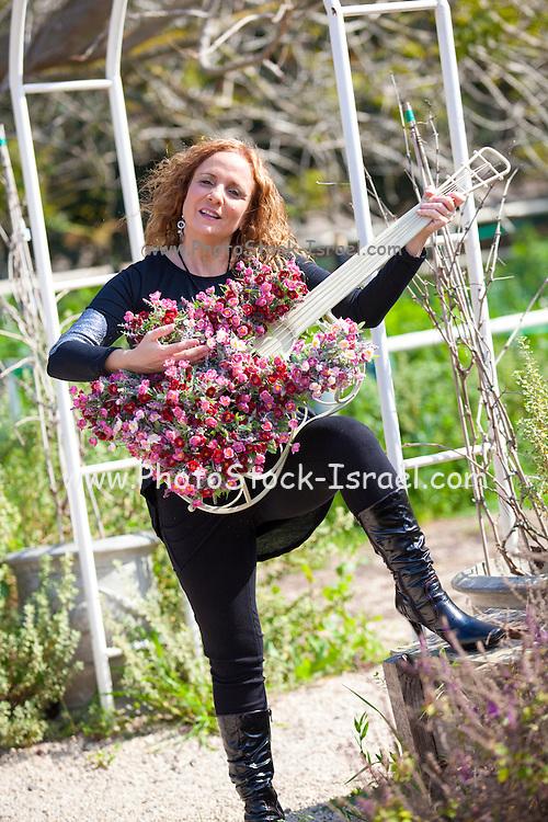 Woman with a guitar shaped flowerpot in her garden