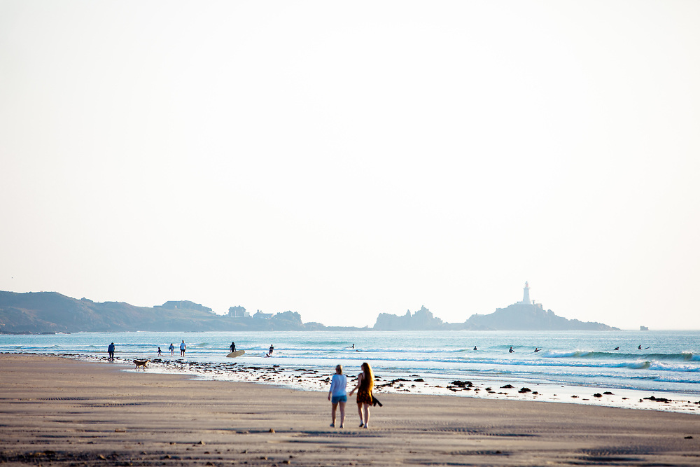 Friends walking along the shoreline at St Ouen's Bay with views of the tourist attraction Corbiere lighthouse in the distance and surfers in the sea in Jersey, Channel Islands