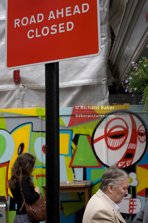 Road Ahead Closed sign and modern city art on construction hoarding in London's Soho.