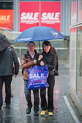 © Licensed to London News Pictures . 26/12/2015 . Manchester , UK . A couple with a shopping bag walk through the rain in Manchester this morning (26th December 2015) . Photo credit: Joel Goodman/LNP