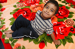 Portrait of young boy sitting on a rug smiling,