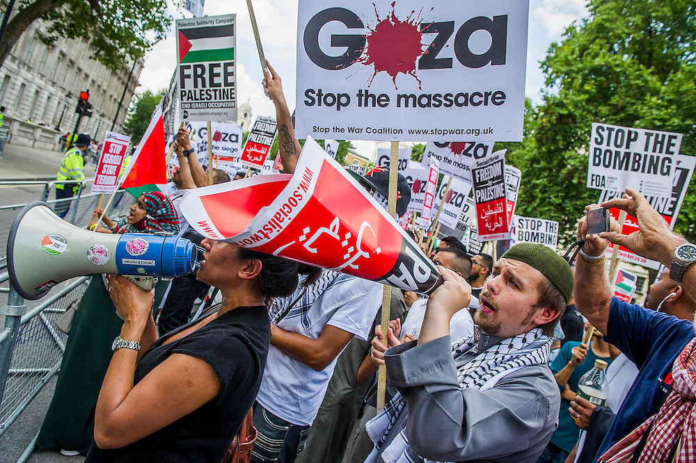 """The March Passes Downing Street. Stop the 'massacre' in Gaza protest. A demonstration called by: Stop the War Coalition, Palestine Solidarity Campaign, Campaign for Nuclear Disarmament, Friends of Al Aqsa, British Muslim Initiative, Muslim Association of Britain, Palestinian Forum in Britain. They assembled at the Israeli Embassy and marched to Parliament. They called for """"Israel's bombing and killing to stop now and for David Cameron to stop supporting Israeli war crimes"""". London, 26 July 2014. Guy Bell, 07771 786236, guy@gbphotos.com"""