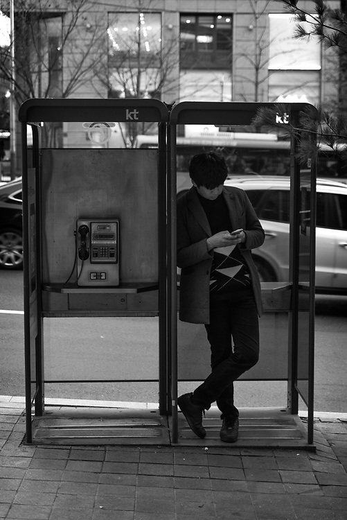 A man uses his cellphone while in a Telephone Booth in Gangnam, Seoul, South Korea