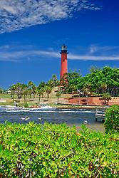 Jupiter Inlet Lighthouse, restored 1860 historic lightouse, and sport fishing boats in Loxahatchee River, Florida, Atlantic Ocean