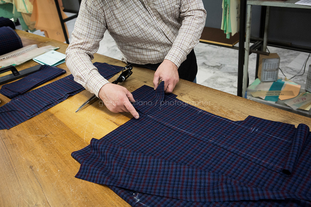ARZANO, ITALY - 16 January 2014:  A tailor works on a fabric used for a jacket at the Kiton factory in Arzano, Italy, on January 16th 2014.