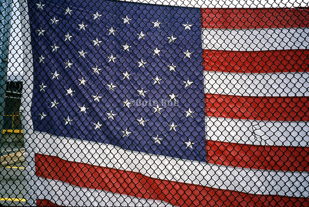 Detail of a flag hanging behind a fence