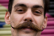 A close-up portrait of a young man in his late-twenties street portrait with moustache. The mustache is well-waxed to keep its upturned shape and is generally known as a handlebar style of facial growth. Focus is on the curled hair and eyes rather than on his clothing and urban background. The fellow is stylish and is very self-confident as he makes a bold statement of his own youth and gender.