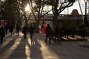 Sun setting behind trees casting low shadows on the riverside walkway on the Southbank, London, United Kingdom. The South Bank is a significant arts and entertainment district, and home to an endless list of activities for Londoners, visitors and tourists alike.
