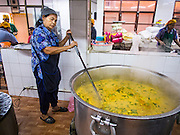 """08 FEBRUARY 2015  BANGKOK, THAILAND: A woman makes a vegetable curry in the kitchen before the communal meal at the Gurdwara Siri Guru Singh Sabha in Bangkok. Thailand has a small but influential Sikh community. Sikhs started coming to Thailand, then Siam, in the 1890s. There are now several thousand Thai-Indian Sikh families. Gurdwara Siri Guru Singh Sabha was established in 1913. Construction of the current building, adjacent to the original Gurdwara (""""Gateway to the Guru""""), started in 1979 and was finished in 1981. The Sikh community serves a daily free vegetarian meal at the Gurdwara that is available to people of any faith and background.    PHOTO BY JACK KURTZ"""