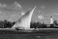 Dhow Boat sailing past lighthouse on Zanzibar