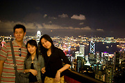 Three Chinese tourists pose to have their photograph taken from the Victoria Peak viewing platform. As night falls from this classic viewpoint the entire view across Hong Kong Harbour can be seen. The view sweeping down through Mid-levels to Central, along to Causeway Bay, all the way along Hong Kong Island's coast across North Point, Quarry Bay to Wan Chai. Also over the water we see the Chinese mainland area Kowloon.