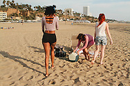 Three pretty young women packing up after a day at the beach.