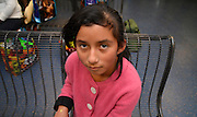 Tucson, Arizona, USA, June 26, 2014: An 11-year-old Guatemalan girl waits with her mother in Tucson at bus station where she was dropped off by the U.S. Border Patrol after being apprehended near Douglas, Arizona, USA, where they crossed the border illegally from Mexico.  The two traveled for about five days from Guatemala to get to the Arizona border.  They, along with others, heard in Guatemala that mothers with children could find work in the U.S. and better their lives.  Recently flooded with undocumented migrants from Central America, federal authorities are transporting children with adults to bus stations where they will head to other states in the U.S.  Their status in the U.S. will be addressed by authorities after they reach their destination.
