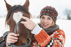 Portrait of a young woman adjusting horse bridle for riding in winter, Bavaria, Germany