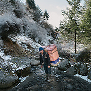 A man carrying a washing machine. On the trek going from Laya village to the beginning of the drivable road.