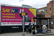 2009 local election. Poster for UKIP (UK Independence Party) with picture of Churchill and slogan 'Say No to unlimited immigration ', in front of a bus stop where black family are waiting for a bus.