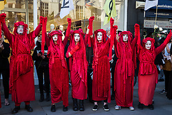 London, UK. 17 September, 2019. Climate activists from Extinction Rebellion pause outside a branch of H&M during a RIP London Fashion Week Funeral March to call on both the public and the fashion industry to demand an end to London Fashion Week and the unsustainable system of consumption which it promotes. The event included a pause to reflect on the lives already lost and those that will be lost as a result of the climate and ecological crisis. Credit: Mark Kerrison/Alamy Live News