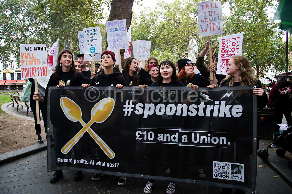 Food service industry workers strike for higher wages on October 4th 2018 in Leicester Square, London, United Kingdom. Day of action by workers from TGI Fridays, McDonalds; Deliveroo and Wetherspoons, supported by TUC and Labour Party, demanding better conditions for the hospitality sector. A group of Wetherspoon workers protest behind a banner demanding a £10 per hour wage.