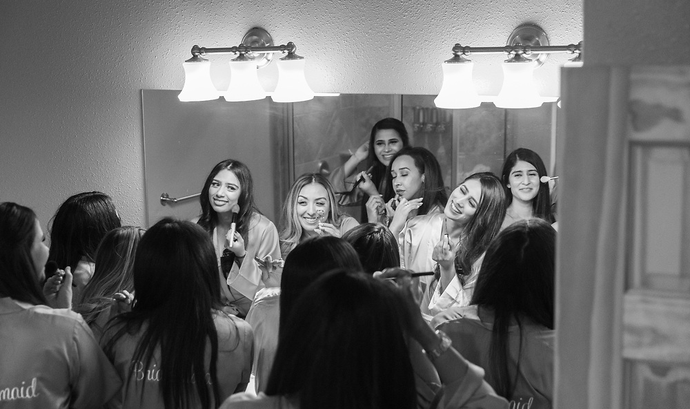 Bridesmaids getting ready in their room, having fun in black and white.