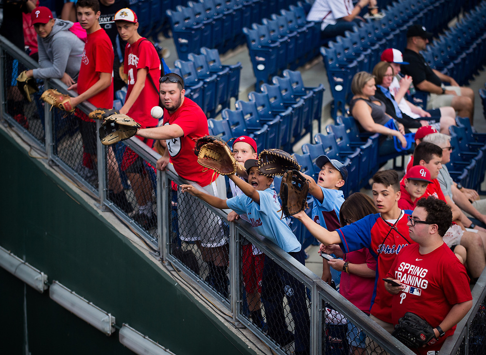 Young fans stretch to catch a ball thrown to them from the bullpen before the Phillies play the Braves.