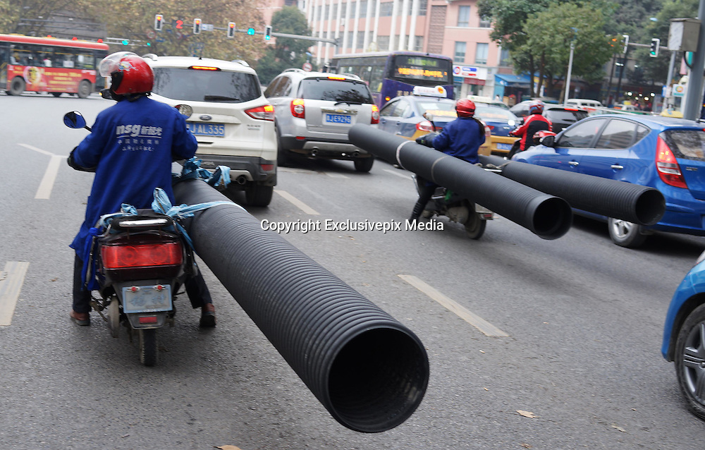 """GUIYANG, CHINA - DECEMBER 10: (CHINA OUT) <br /> <br /> Woman rides motorbike carrying hugh tubular products<br /> <br /> A woman rides a motorcycle carrying tubular products at Baoshan North road on December 10, 2014 in Guiyang, Guizhou province of China. A woman rides a motorcycle carrying tubular products was called """"The best motorcycle rider"""" in Guiyang on Wednesday. <br /> ©Exclusivepix Media"""