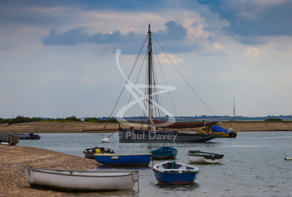 Dark clouds slowly drift northwards above moored boats in the Blackwater Estuary, with the prospect of a spectacular sunset in store at West Mersea, Mersea Island, near Colchester in Essex. West Mersea, Essex, July 10 2019.