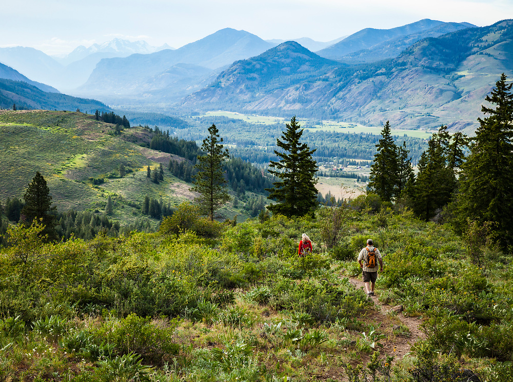 A man and woman hiking down Patterson Mountain with the Methow Valley below and the Cascade mountains in the distance, Washington, USA.