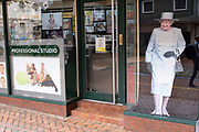 Cut out print of Her Majesty Queen Elizabeth II looks out from a printing shop in the city centre as a worker inside engages with her job on 18th August 2020 in Birmingham, United Kingdom.
