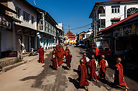 Young monks walk down a quiet street in the early morning in northern Shan State, Myanmar.