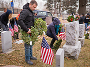 14 DECEMBER 2019 - DES MOINES, IOWA: Volunteers place Christmas wreaths on veterans' graves. Volunteers working with Wreaths Across America placed Christmas wreaths on the headstones of more than 600 US military veterans in Woodland Cemetery in Des Moines. The cemetery, one of the first in Des Moines, has the graves of veterans going back to the War of 1812.      PHOTO BY JACK KURTZ