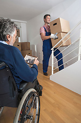 Handicapped old man looking at photograph and removal man carrying cardboard box upstairs, Bavaria, Germany