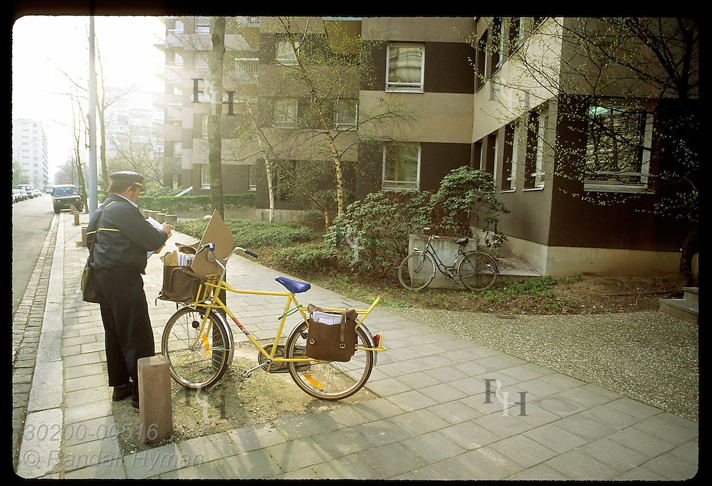 Postman sorts mail in the early morn after parking bike outside apartment building; Strasbourg. France