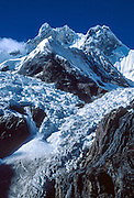 """Glaciers crack and ice falls in a small avalanche from Mount Jirishanca, or the """"Icy Beak of the Hummingbird"""" (west face, 6126 m or 20,098 feet elevation), third highest in the Cordillera Huayhuash, tenth highest in Peru. Andes Mountains, South America."""