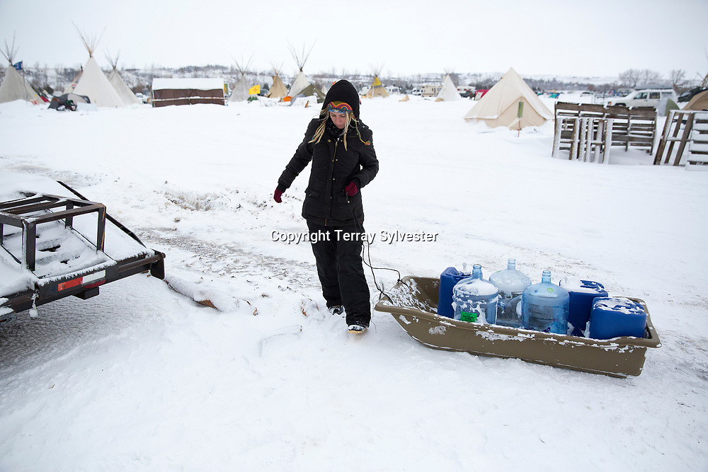 Lindsey Eckenrode from Baltimore, Maryland, searches for drinking water during winter weather in the opposition camp against the Dakota Access oil pipeline on November 30, 2016. Cannon Ball, North Dakota, United States.