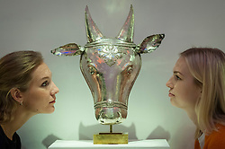 © Licensed to London News Pictures. 20/10/2017. London, UK. Staff members view a South Indian large silver tribal or ritual mask of Nandi, 18th century, (GBP10-15k) at a preview of Islamic, Middle Eastern and other artworks which be auctioned at Sotheby's New Bond Street on 24 and 25 October. Photo credit : Stephen Chung/LNP