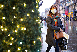 Glasgow, Scotland, UK. 20 November 2020. On the day when the severest level 4 lockdown will be imposed at 6pm, shoppers are out on the streets of Glasgow doing last minute Christmas shopping before the shops close for 3 weeks. Pictured; Woman shopping on Buchanan Street.  Iain Masterton/Alamy Live News