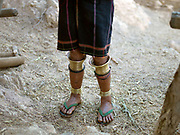 A Kayaw ethnic minority woman wearing brass leg rings on 19th January 2016 in Kayah State, Myanmar. Wearing traditional costumes made from handwoven cotton, Kayaw women wear many necklaces made from shells, beads and brass coils and fashioned from silver. Distended earlobes are plugged with rings of silver and the ankles and knees encased with brass coils
