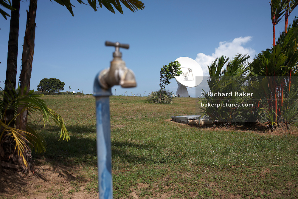 A hot tropical landscape with water tap and satellite tracking dish at the VT Merlin Diane Tracking station, French Guiana