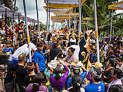 16 JULY 2016 - UBUD, BALI, INDONESIA: People place the effigy of the person being cremated and offerings left for him into his sarcophagus at the mass cremation in Ubud. Local people in Ubud exhumed the remains of family members and burned their remains in a mass cremation ceremony Wednesday. Almost 100 people were cremated and laid to rest in the largest mass cremation in Bali in years this week. Most of the people on Bali are Hindus. Traditional cremations in Bali are very expensive, so communities usually hold one mass cremation approximately every five years. The cremation in Ubud concluded Saturday, with a large community ceremony.     PHOTO BY JACK KURTZ