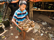 30 OCTOBER 2015 - TWANTE, MYANMAR: A boy carries pottery out to dry it in the sun in the potters' village in Twante, (also spelled Twantay) Myanmar. Twante, about 20 miles from Yangon, is best known for its traditional pottery. The pottery makers are struggling to keep workers in their sheds though. As Myanmar opens up to outside investments and its economy expands, young people are moving to Yangon to take jobs in the better paying tourist industry or in the factories that are springing up around Yangon.     PHOTO BY JACK KURTZ