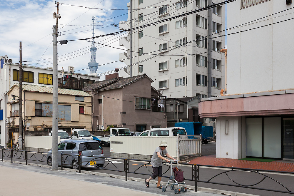 An older Japanese woman walks on a street with the tower of Tokyo Skytree behind. Asakusa, Tokyo, Japan Thursday June 28th 2018