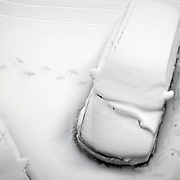 A car snowed in, in a blanket of snow with footprints coming from the drivers door walking away from the car.
