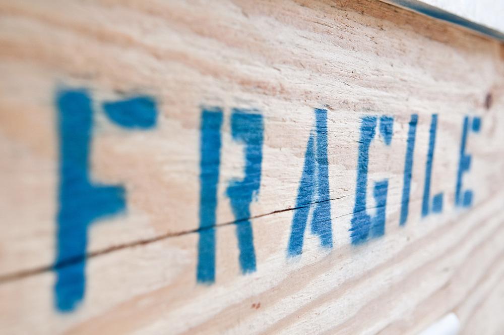 Fragile steht in riesigen blauen Buchstaben auf einer Holzkiste für Kunsttransporte | engl. Fragile is written in huge blue letters on a wooden box for art transportation