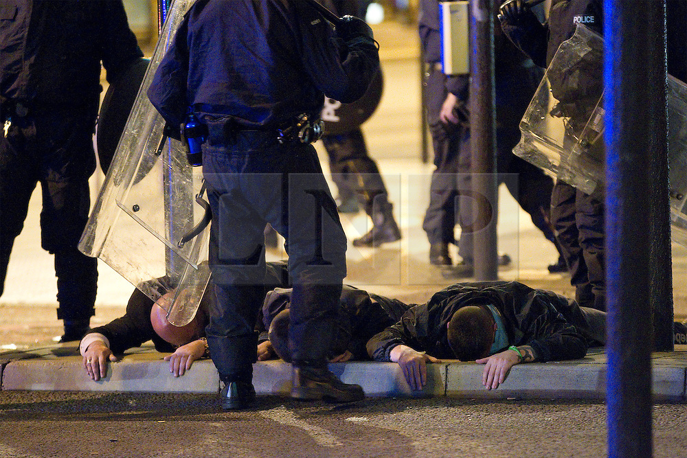 """© Licensed to London News Pictures . FILE PICTURE DATED 09/08/2011 .  Manchester , UK . DOMENYK NOONAN (pictured lying face down, first on the left, being detained by police during riots in Manchester City Centre on 9th August 2011) has been arrested on suspicion of imprisoning and raping a 15 year old boy . Police were called to a flat in Manchester City Centre on the afternoon of Wednesday (24th October). The organised crime boss and star of documentary """"At Home With the Noonans"""" is one of three people under arrest for false imprisonment and rape . Noonan, who also goes under the name Lattlay-Fottfoy, is a cousin of Mark Duggan , whose shooting sparked off riots in London in the summer of 2011 . Photo credit : Joel Goodman/LNP"""