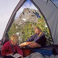 A mother and her son relax by their tent in Big Pine Canyon, part of the  John Muir Wilderness in California's Sierra Nevada.  Behind is Mount Robinson of the Palisade Crest.