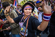 """14 JANUARY 2014 - BANGKOK, THAILAND: Anti-government protestors play drums and dance on Rama I Road in front of Royal Thai Police headquarters. Hundreds of protestors picketed police headquarters because they accuse the police of siding with the government during the protests. Tens of thousands of Thai anti-government protestors continued to block the streets of Bangkok Tuesday to shut down the Thai capitol. The protest, """"Shutdown Bangkok,"""" is expected to last at least a week. Shutdown Bangkok is organized by People's Democratic Reform Committee (PRDC). It's a continuation of protests that started in early November. There have been shootings almost every night at different protests sites around Bangkok, but so far Shutdown Bangkok has been peaceful. The malls in Bangkok are still open but many other businesses are closed and mass transit is swamped with both protestors and people who had to use mass transit because the roads were blocked.     PHOTO BY JACK KURTZ"""