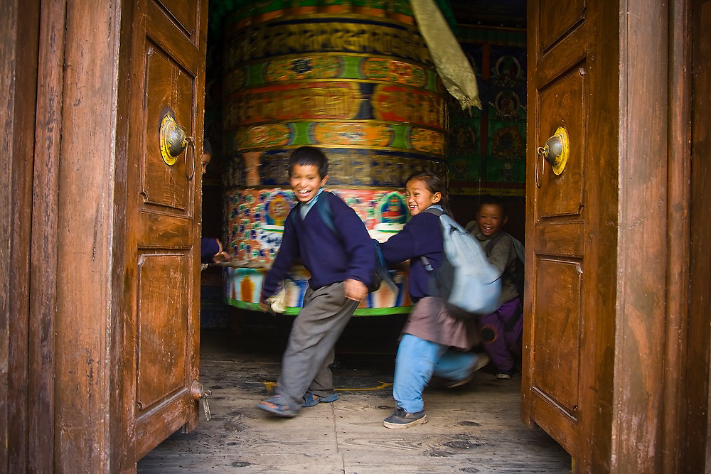School children spin a giant prayer wheel on their way back home from school in Phakding, Khumbu (Everest) region, Himalaya Mountains, Nepal.